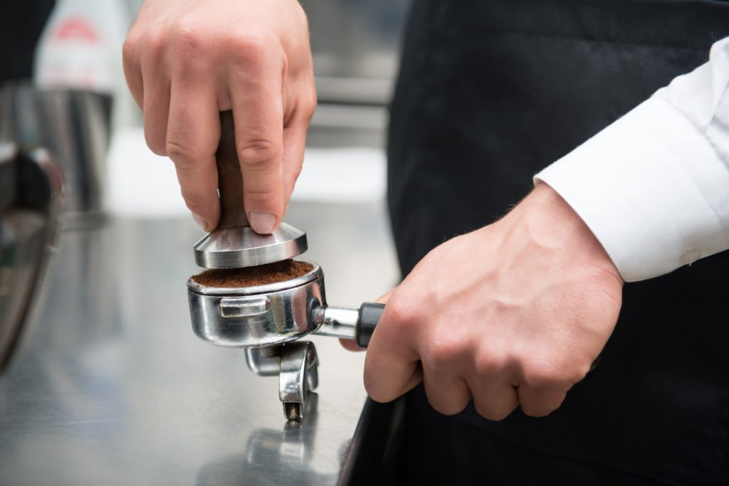 Selected focus on the hands of professional barista pressing coffee using the pounder with wooden handle. Coffee machine on background